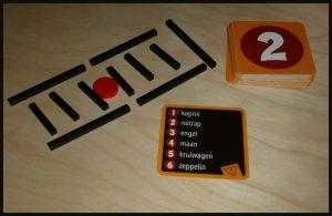 Wazzda?! 8+ White Goblin Games familiespel eenvoudig direct speelklaar uitbeelden opdrachten kaarten houten staafjes cirkels grappig lachen team twee spelers speel snel recensie review